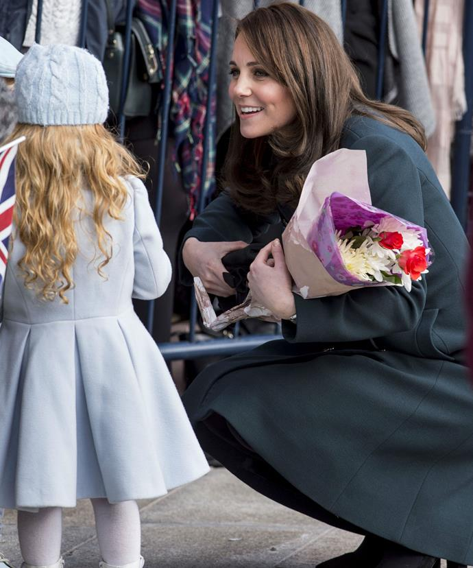 Kate, who is seven months pregnant, was pictured bending down to chat with one very little well-wisher.