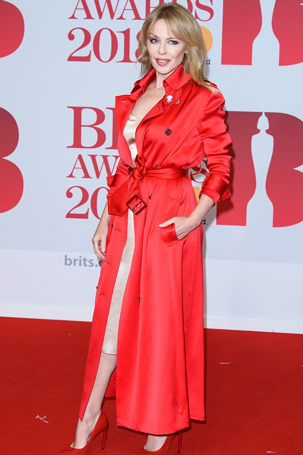Kylie Minogue did not disappoint in a luxurious red Ralph & Russo trench coat that revealed a hint of a silk slip.