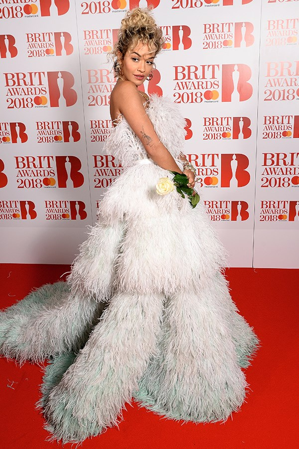 Rita Ora makes a great case for a perm and plenty of feathers here in this showstopping gown. The singer wowed on the red carpet in the strapless, layered dress that cinched in at the waist and faded from white into ice-blue at the hem.