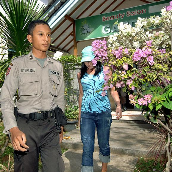 Schapelle Corby is escorted by a policeman as she leaves a beauty salon in Denpasar, July 2008.