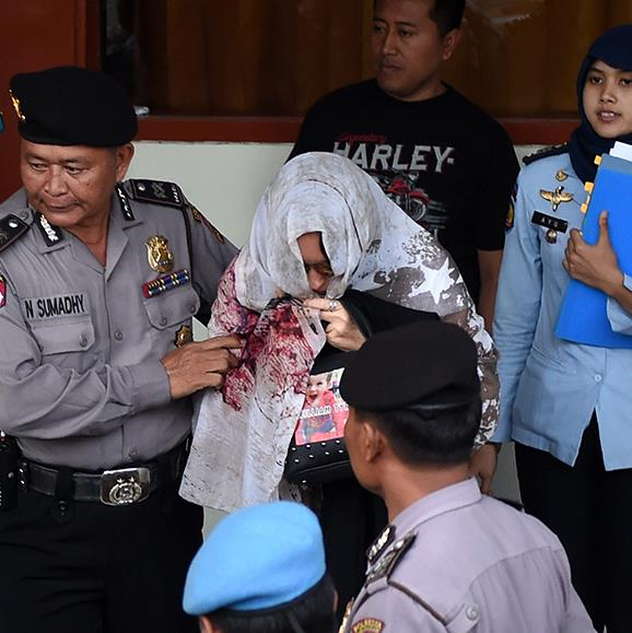 Schapelle Corby, seen with her face obscured with a shawl, is escorted by officials as she makes her way home to Australia, May 2017.