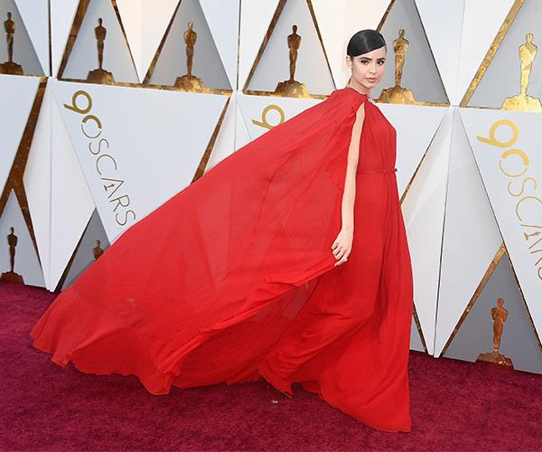 Singer/actress Sofia Carson is a total vision in this flowing red dress with an elegant cape.