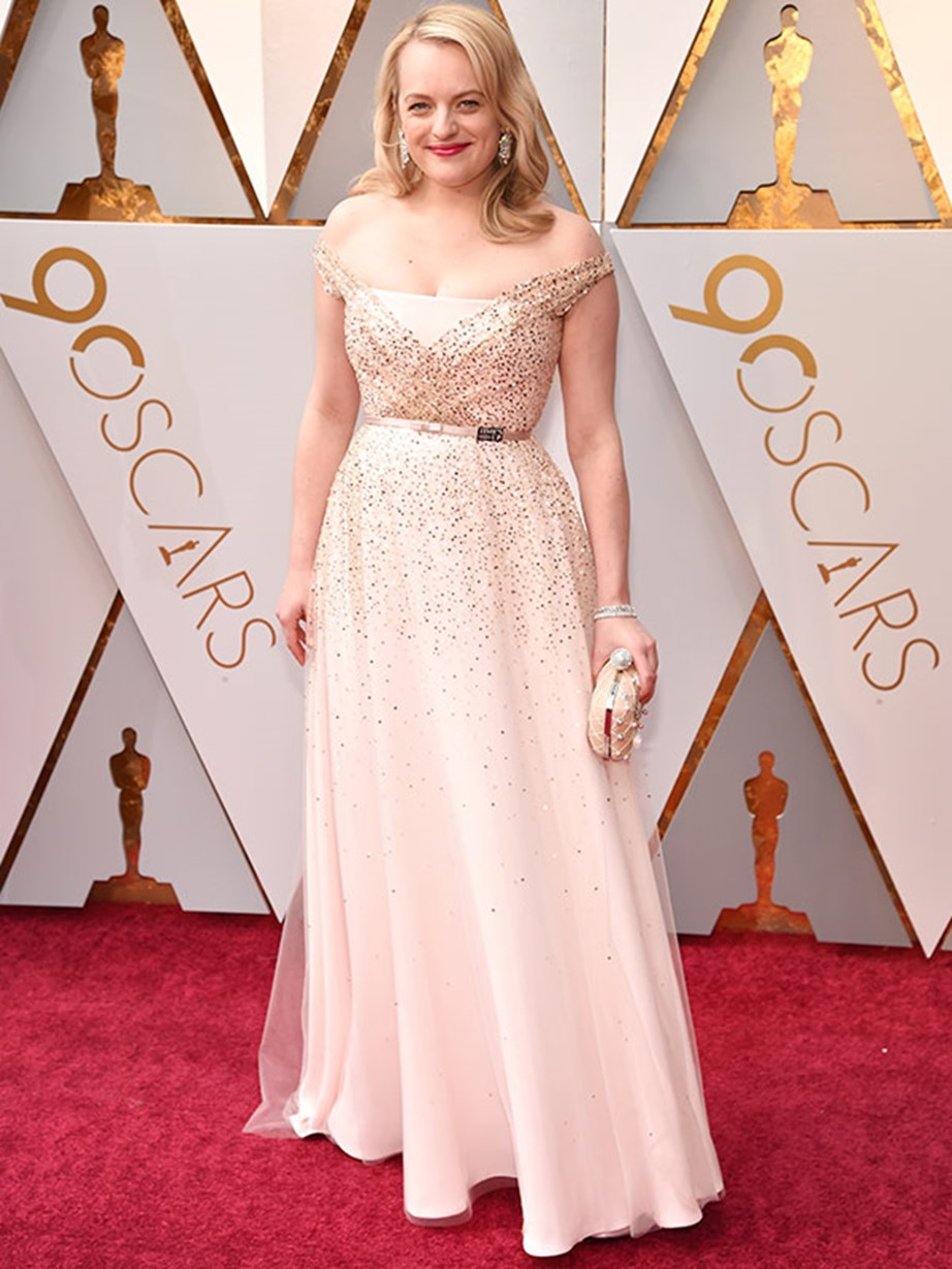 Elisabeth Moss dons a #TimesUp pin on the belt of her dress.