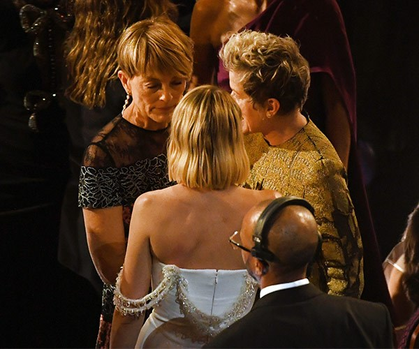 Good sports! Margot Robbie and her mum talk to fellow Best Actress nominee, Frances McDormand.