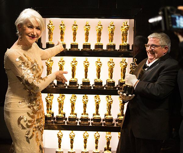 Helen Mirren shows off the wall of Oscars.