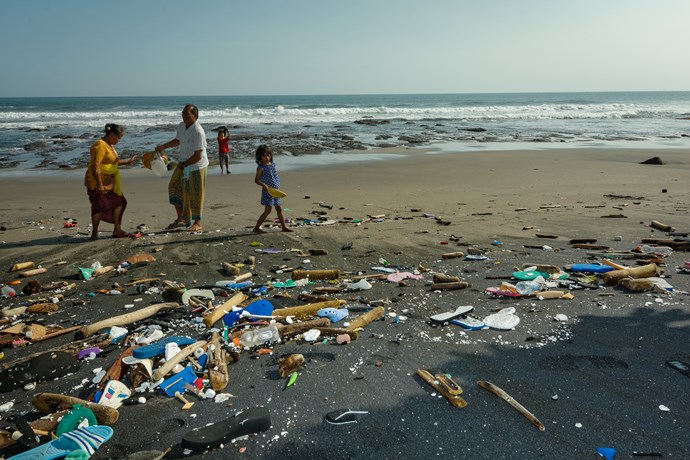 A Balinese family walks in the beach amidst plastic waste.