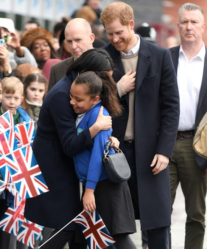 Meghan broke royal protocol to share a cuddle with the youngster.