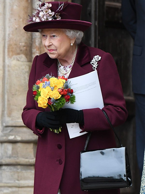 Her Majesty chose a deep burgundy ensemble for the formal event. She accented the look with her trusty patent leather handbag.