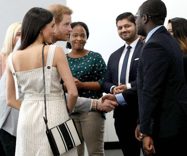 Harry and Meghan speak to young delegates at the Commonwealth Youth Forum in April 2018. *(Image: Getty)*