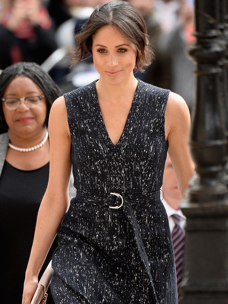 Meghan wore a demure black Hugo Boss dress cinched in at the waist with a metallic buckle.