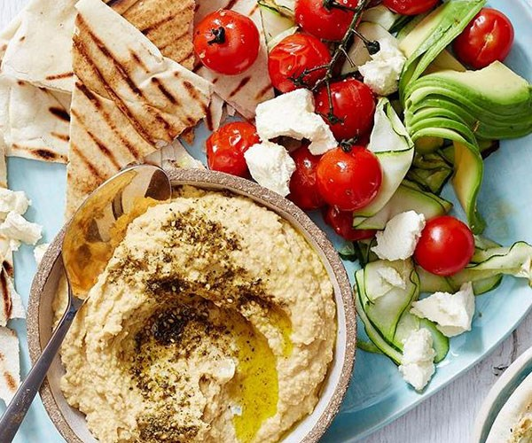 Serve hummus with toasted flatbread, roasted tomatoes and zucchini, sliced avocado and crumbled feta.