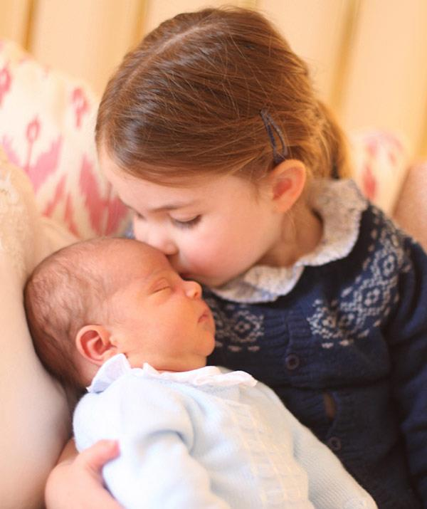 Prince Charlotte poses with her new brother Prince Louis for his first portrait taken by mum Duchess Catherine.