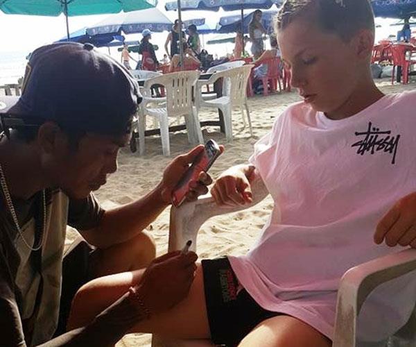 Drew getting a henna tattoo on a beach in Bali.