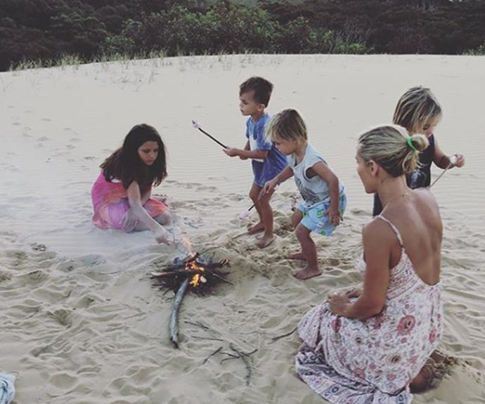 Elsa shows her twin boys and family friend's kids how to build a beach fire.