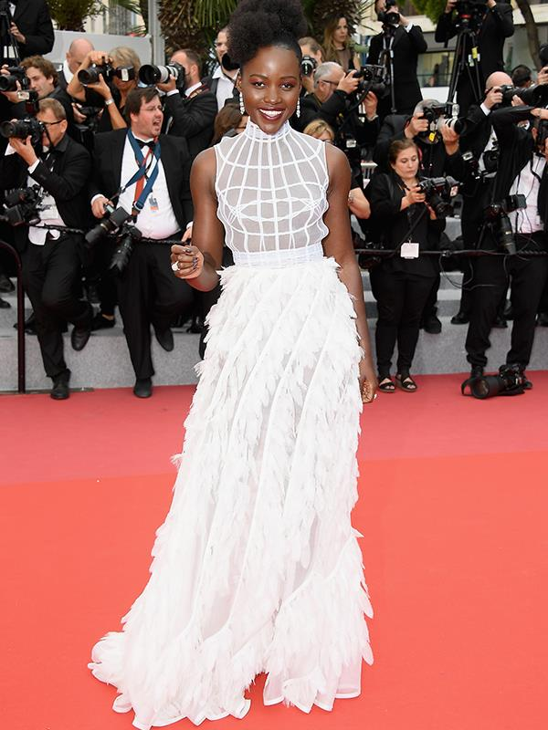 Lupita Nyong'o stuns in a sheer white gown at the Cannes premier of *Sorry Angel*.