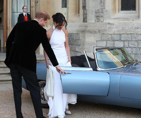 Always the gentleman! Harry helps his new-wife into the swanky ride.