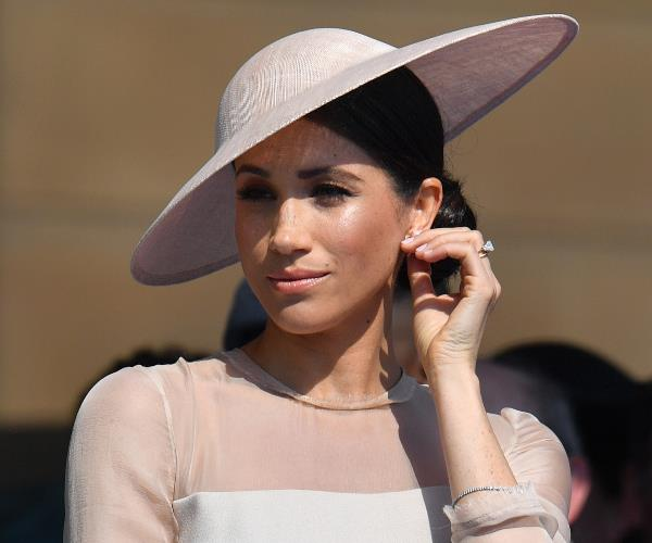 Meghan looked every bit the royal in a pale pink-and-taupe silk-crepe design by Goat.