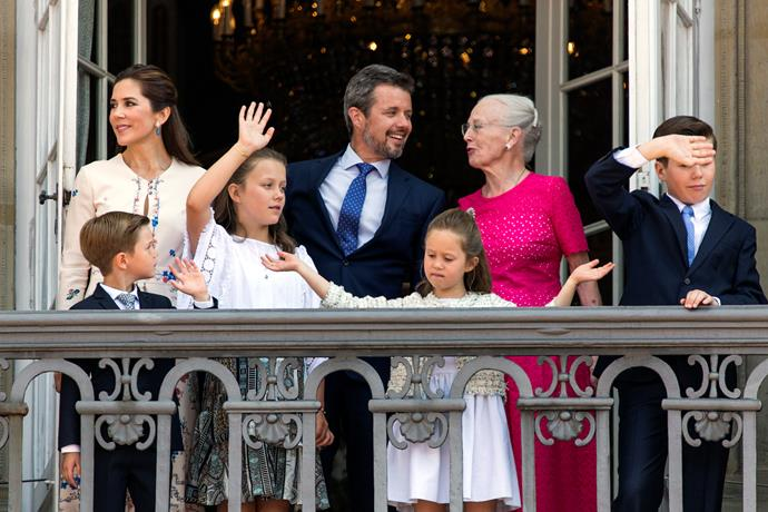 Waving to the public below, joined by Queen Margrethe