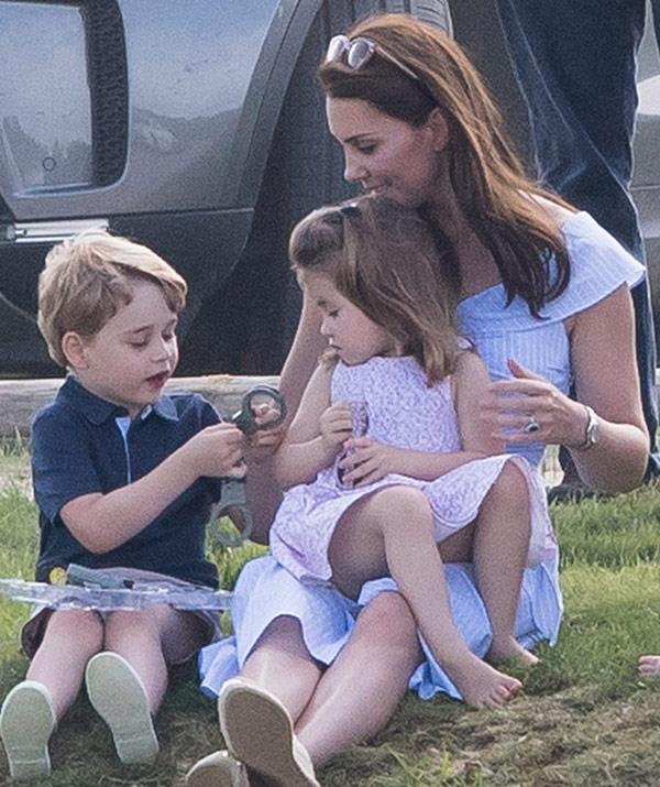 Police-mad Prince George plays with a pair of toy hand-cuffs.