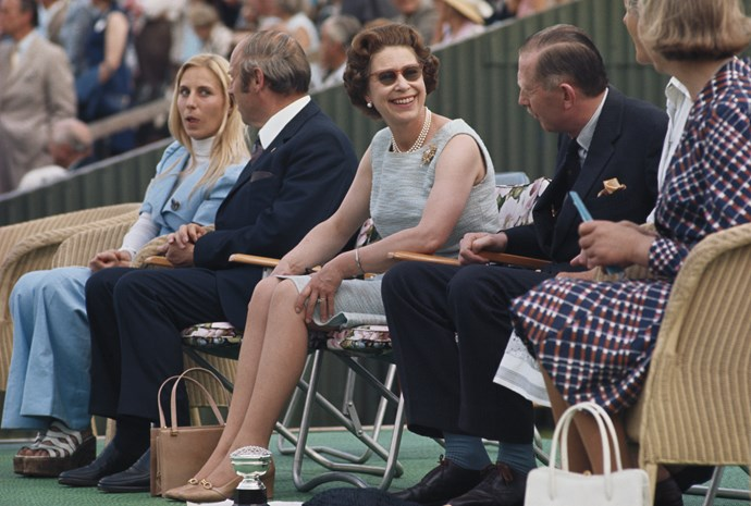Queen Elizabeth II, wearing a chic pair of shades, turns to talk to friends while watching the polo at Smith's Lawn in Windsor, Berkshire, England, Great Britain, circa 1980.
