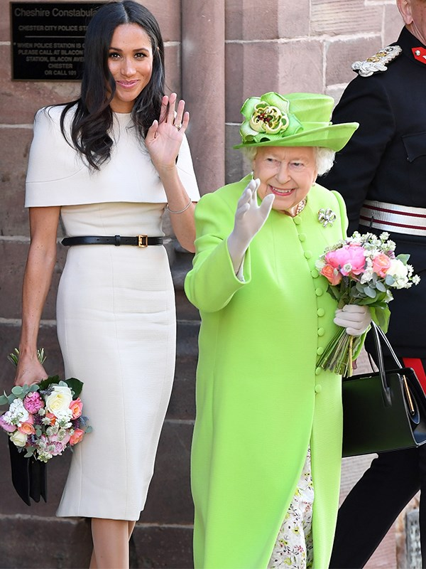 Meghan and The Queen greet waiting fans during their joint appearance at Cheshire last year. *(Image: Getty)*