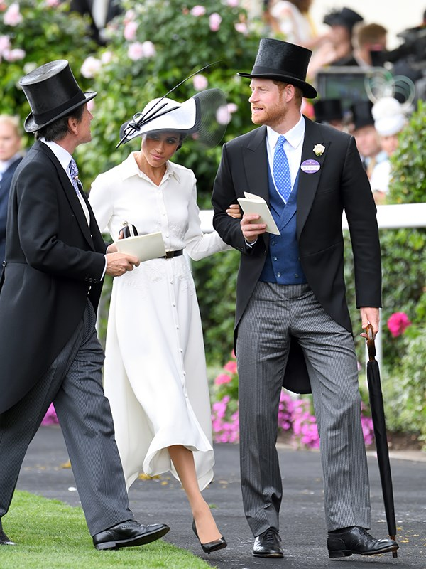 Meghan's shirt dress ticked all the boxes for the strict dress code. She paired her belted ensemble with a hat by Philip Treacy.