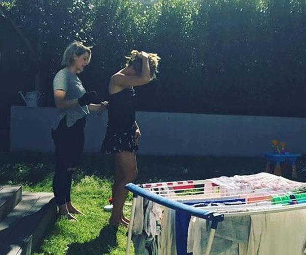 """""""My make up artist Eve @evegunson tanning me in the backyard next to the washing because I ran out of time for spray tan!"""""""