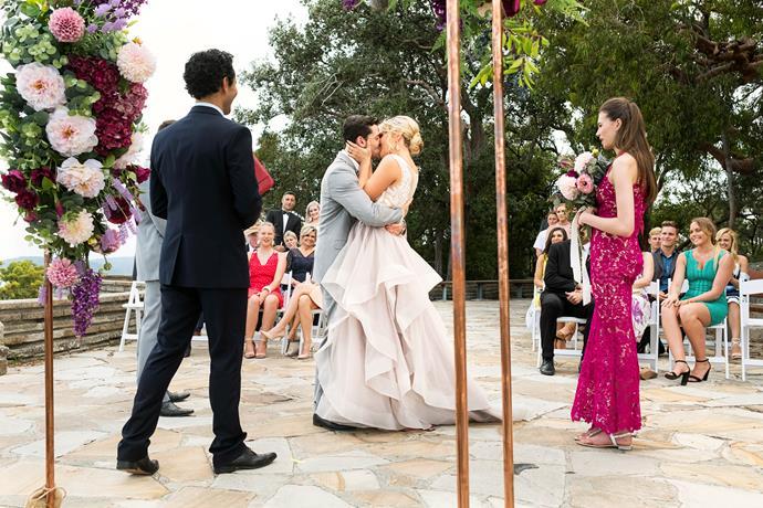 The newlyweds share a passionate kiss.