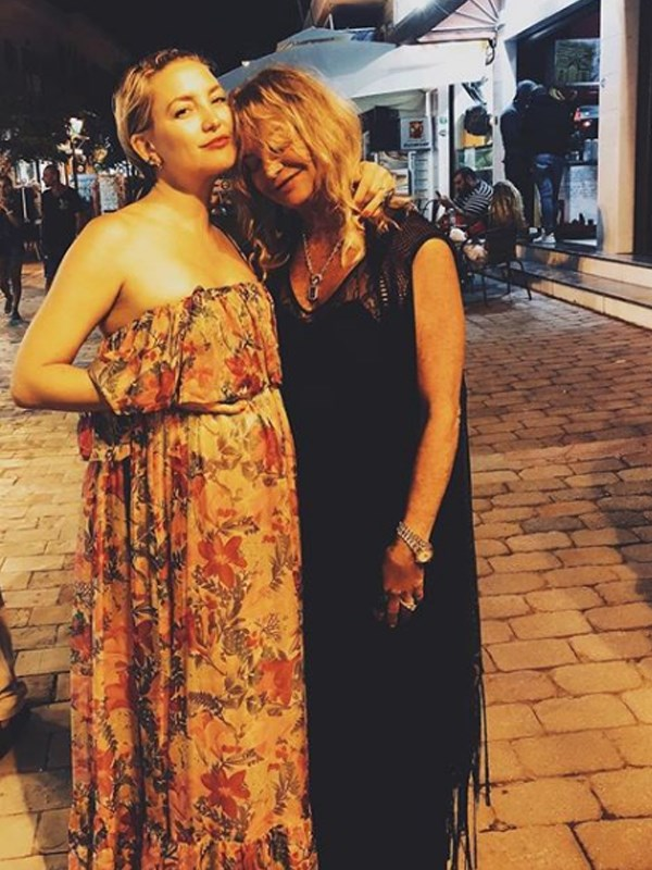 It's a family affair! Kate poses with her mum, actress Goldie Hawn while resting a hand on her baby bump.