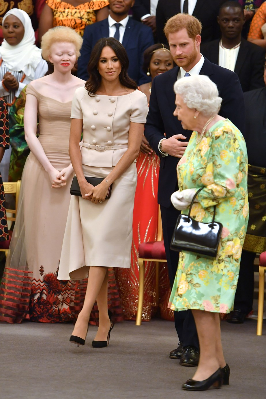 "Powder pink in Prada! Meghan Markle looks as royal as she does sophisticated in this cinched-at-the-waist, buttoned dress at [the Queen's Young Leaders Awards](https://www.nowtolove.com.au/royals/british-royal-family/meghan-markle-queen-elizabeth-queens-young-leaders-awards-ceremony-49458|target=""_blank"") reception at Buckingham Palace. While Meghan looks polished-to-Prada-perfection, we are quietly missing Meghan's ever-so-gently bohemian royal style that she sported pre-wedding. Just saying."