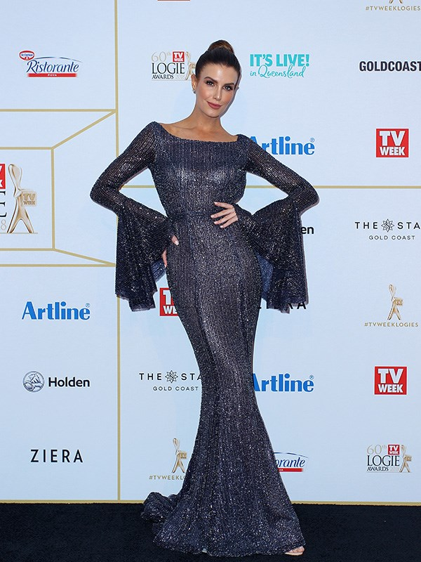 Erin Holland striking a pose in her navy blue, flared-sleeved, *Maleficent*-esque gown.