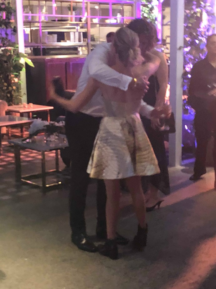 Nick and Sophia sharing a champagne-filled embrace on the Logies D-floor.