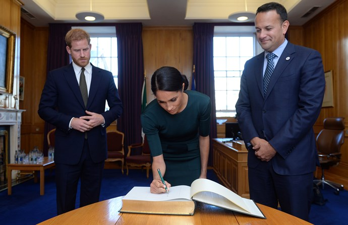 A former calligrapher, Meghan signs her name in the guest book.