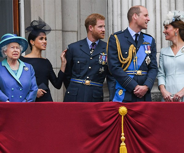 Meghan places her hand on Harry's shoulder.