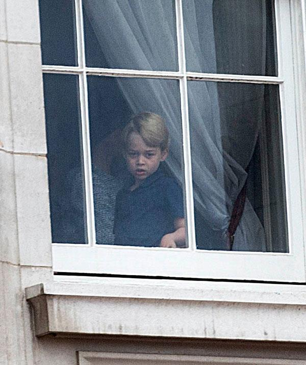 Surprise! Prince George watches on from the window of Buckingham Palace.