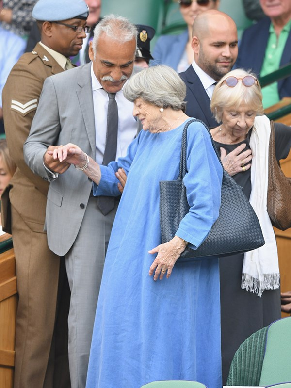 Excuse me, acting royalty coming through! The esteemed actress Maggie Smith is helped to her seat by retired professional tennis player, Mansour Bahrami.