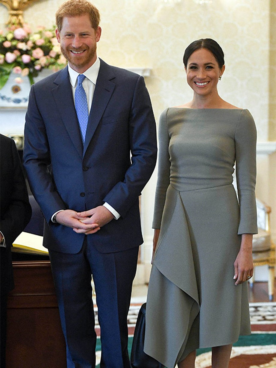 To her visit with the Irish president, Meghan wore a light grey dress with an asymmetrical hemline by designer Rouland Mouret, very similar to the navy blue dress she wore by the same designer the night before her wedding. Meghan also wore Birks earrings, Paul Andrew pumps and a Fendi top-handle bag.