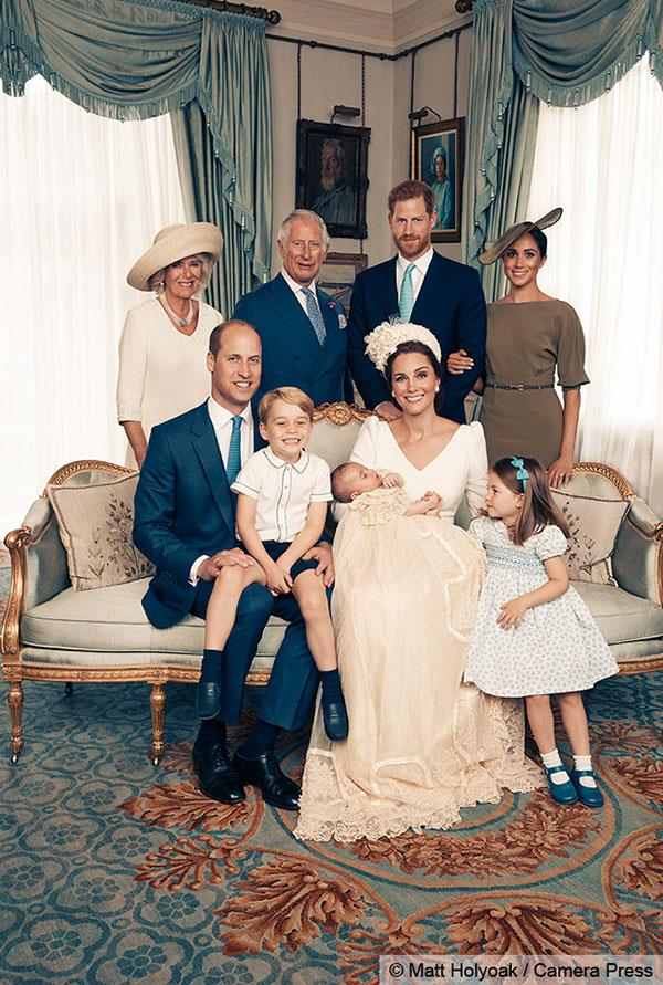 Cheeky George steals the show as he sits on Prince William's lap, while Prince Charles, Duchess Camilla, Prince Harry and the Duchess of Sussex stand proudly behind the 11-week-old.