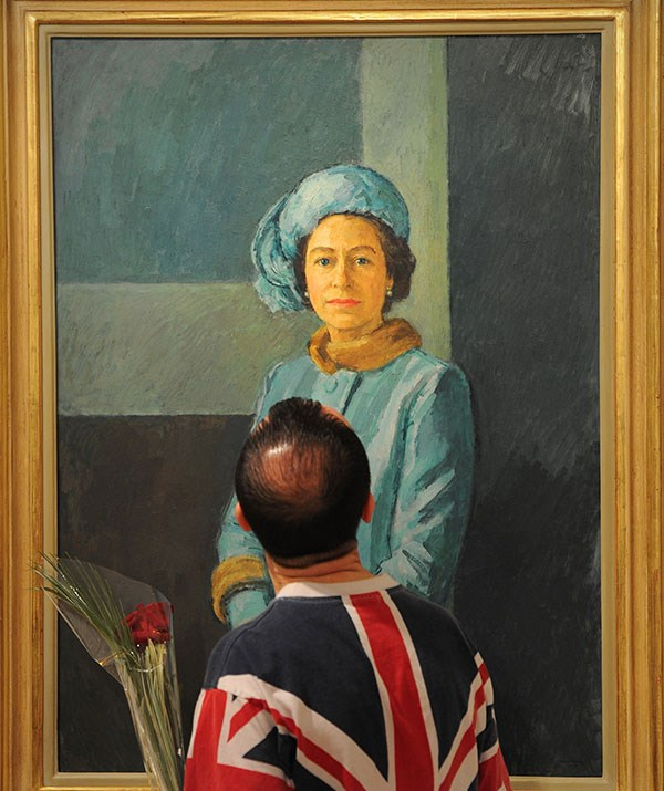 A visitor views a portrait of Britain's Queen Elizabeth II by British artist Michael Noakes during a preview at the Royal Society of Portrait Painters exhibition at the Mall Galleries in London.