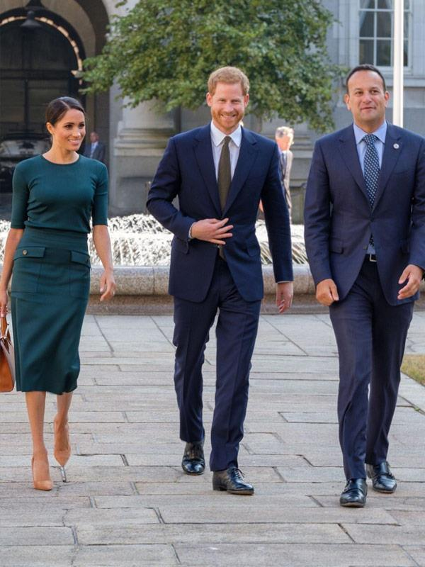 For her arrival in Ireland, Meghan appropriately wore a two-piece dark green piece by Givenchy (who else!), a top-handle tote by Strathberry, Paul Andrew pumps and Vanessa Tugendhaft earrings looking every much the part of a modern royal.
