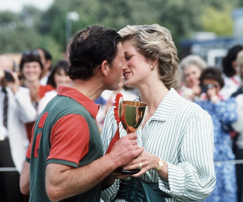 Princess Diana presents Prince Charles with a trophy and a smooch after a polo match.