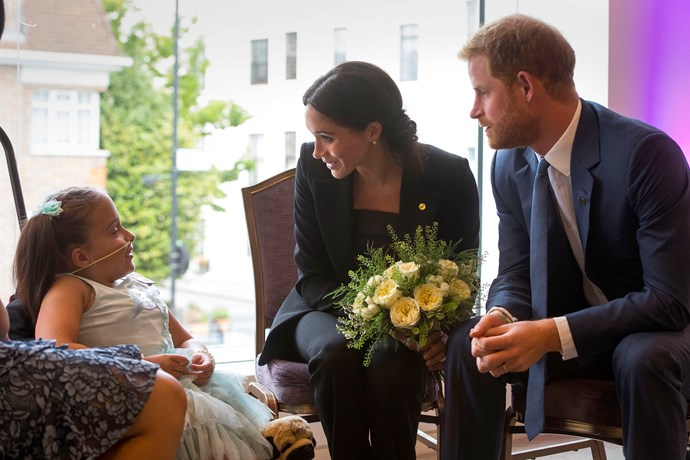 Prince Harry and Duchess Meghan speak to a young girl who suffers from spina bifida.