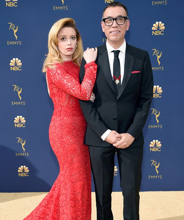 Fred Armisen's red trimmings pay a subtle homage to Natasha Lyonne's bold red dress.