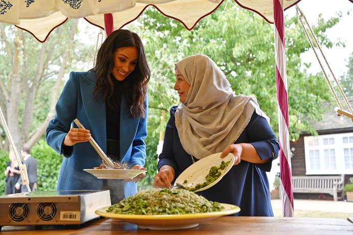 The royal trio worked their way around the event helping the women cook food.