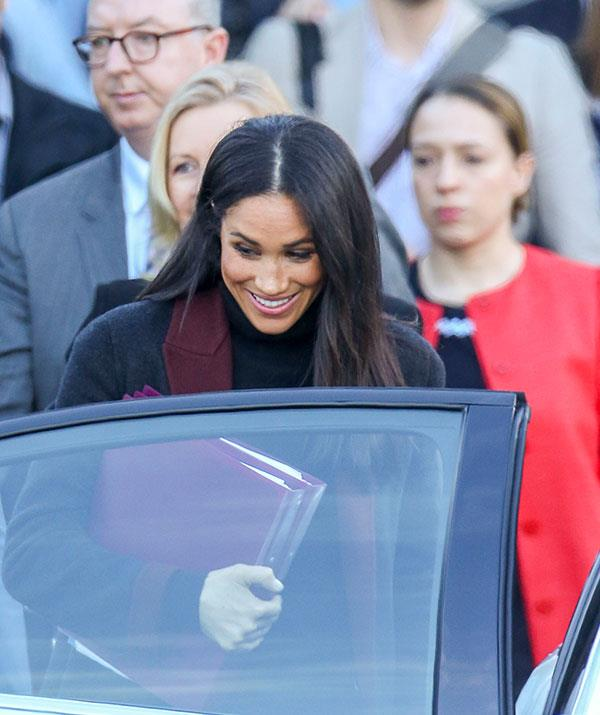 The Duchess cut a stylish figure in a black overcoat with a purple trim. *(Images: Media Mode)*