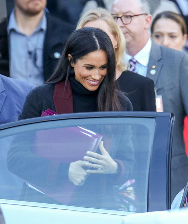 Bump watch: Meghan held the folders across her stomach as she arrived in Sydney this morning.