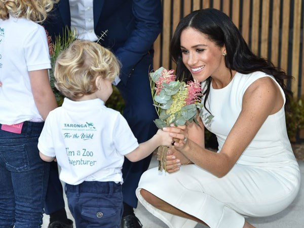 In her high heels and body-con dress Meghan gets down to Findlay's level to receive a posy of Australian natives.