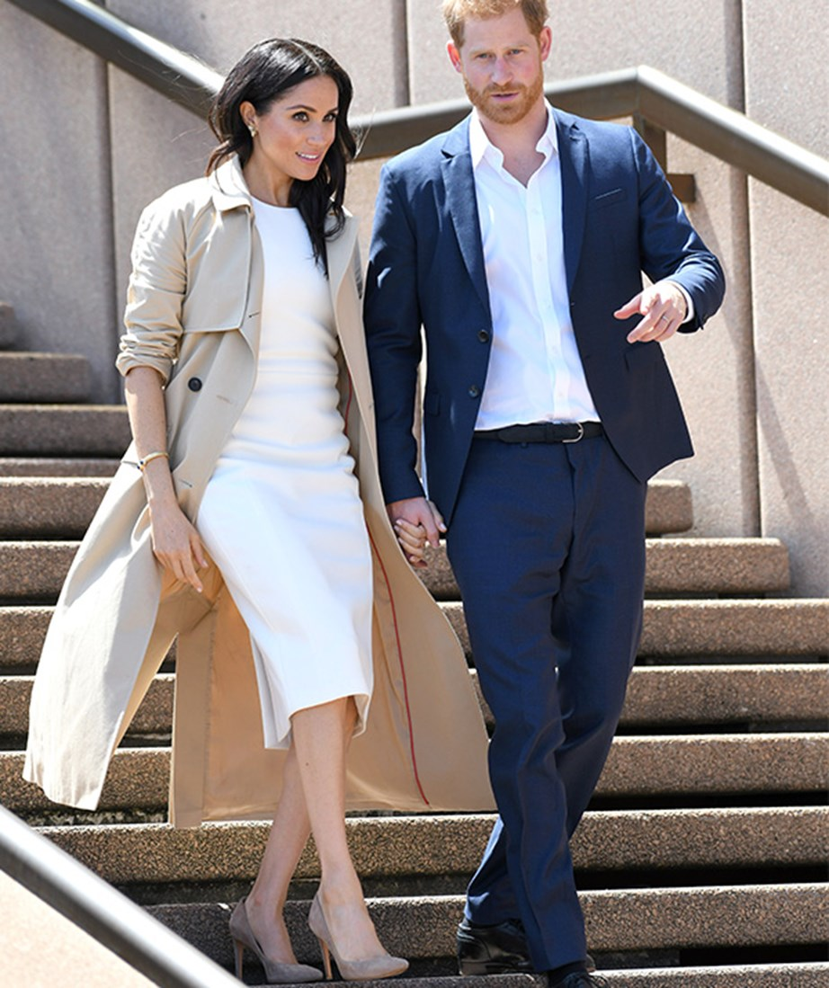Hot off the heels of the exciting announcement that she was expecting her first child with Prince Harry, the Duchess stepped out in Sydney in a chic white Karen Gee dress with she paired with a gorgeous camel coat. *(Image: Getty)*