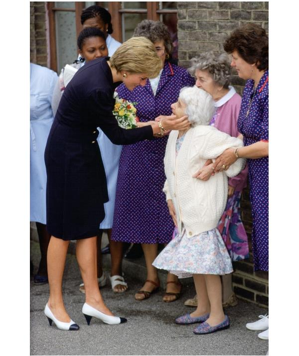 Diana pictured wearing the gold bracelet with blue stones on an official visit to an old people's home in the UK in 1986.  *(Image: Getty)*