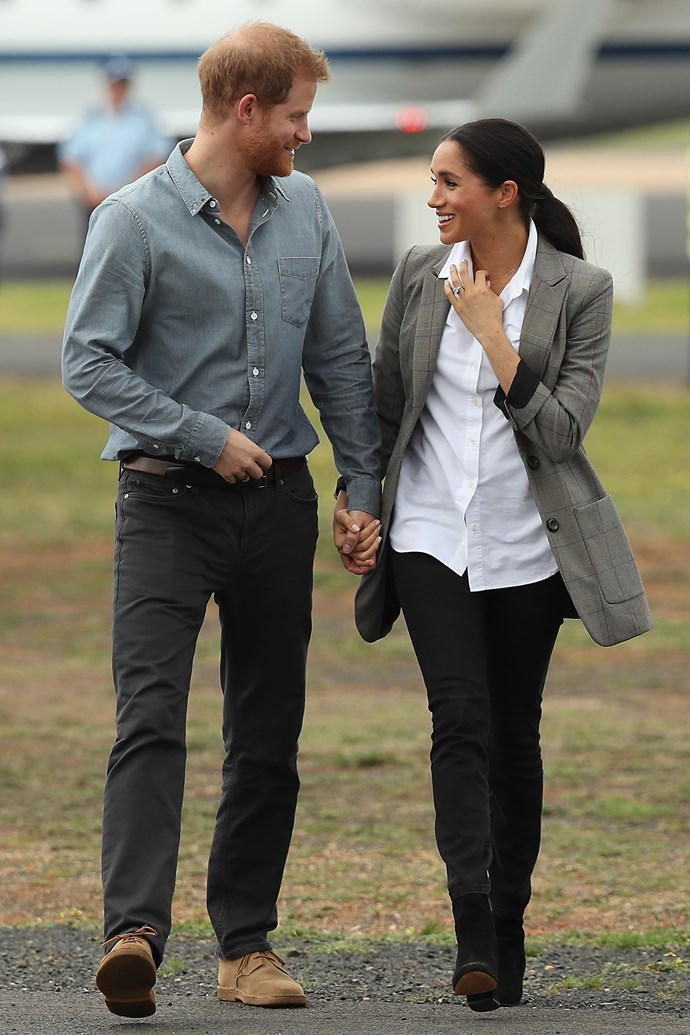 The royals touched down in Dubbo on Wednesday, and the pair looked every bit as country chic as we hoped. Meghan's effortlessly stunning ensemble comprised of black jeans by Australian designer Outlander, paired with a white shirt from Maison Kitsune and a long tailored jacket from pal Serena Williams' Collection. *(Image: Getty Images)*